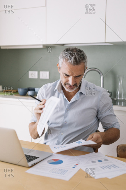 Man analyzing data and using laptop in home office