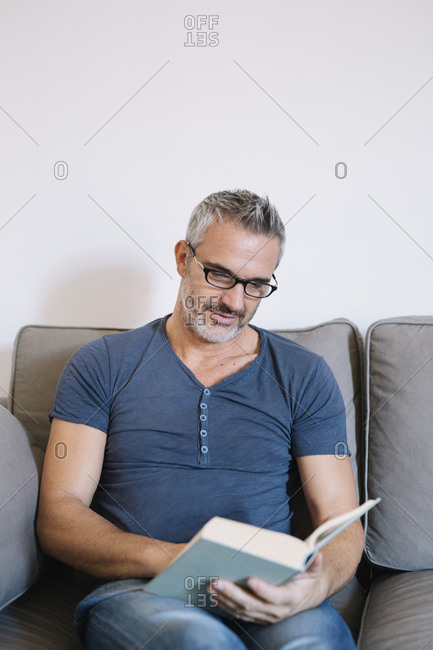 Mature man sitting on couch at home reading book