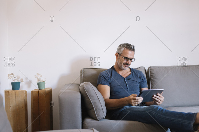 Mature man sitting on couch at home using tablet