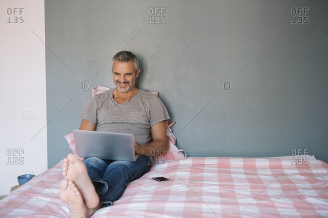 Smiling mature man sitting on bed at home using laptop