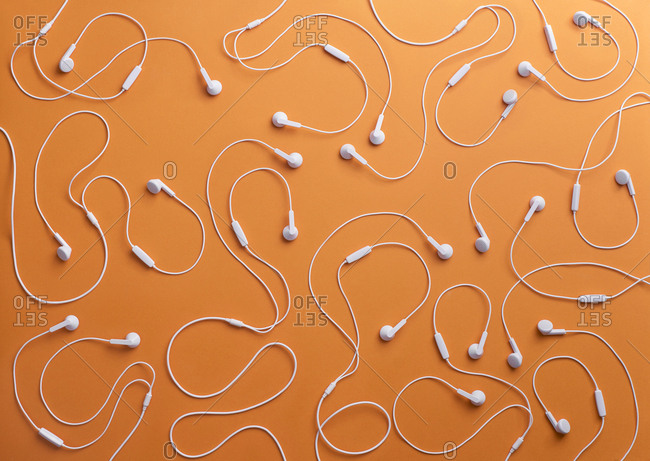 White earphones on orange background- 3D Rendering