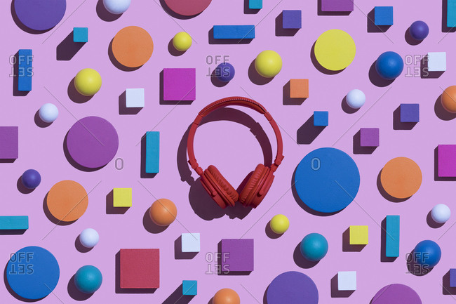 Red wireless headphones surrounded by geometric shapes- 3D Rendering