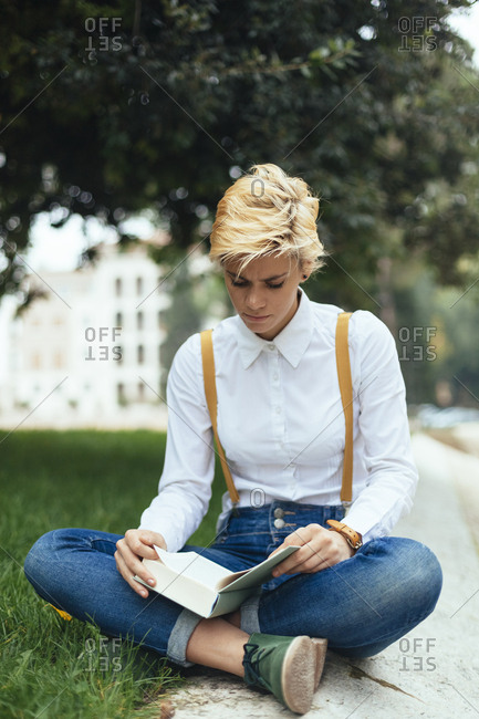 Teenage girl sitting cross-legged in a park- reading book