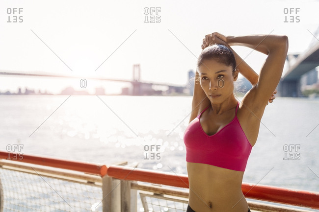 Woman doing stretching exercises in Manhattan near Brooklyn Bridge in the morning