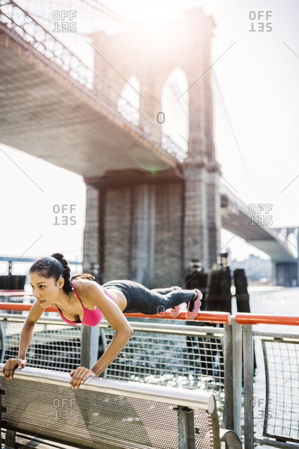 Female athlete training in Manhattan near Brooklyn Bridge- doing push ups on railing