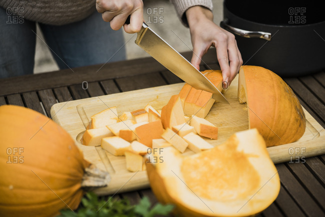 Woman cutting pumpkin on garden table
