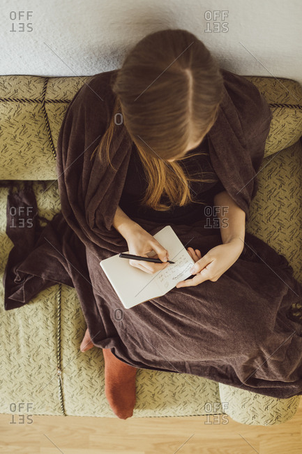 Woman sitting on couch in the living room writing in notebook- top view