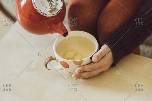 Woman pouring water into tea cup with chopped fresh ginger- close-up