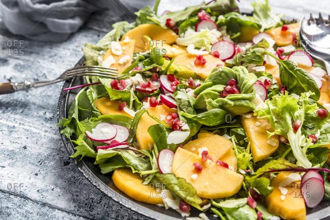 Kaki salad with red radish- pomegranate- avocado and cheese