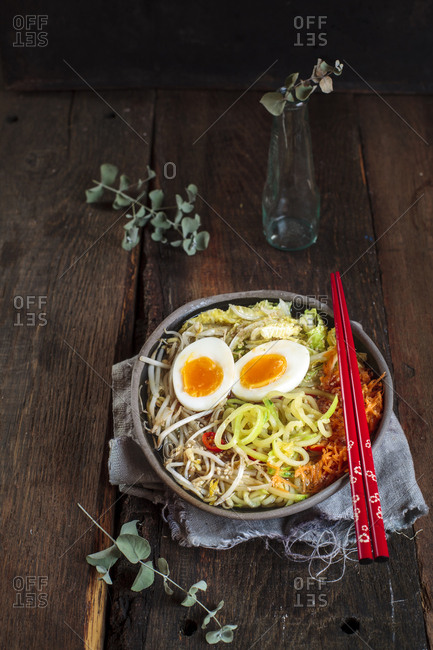 Bowl of gluten free Udon noodle soup with carrots- Chinese cabbage- zoodles- mungo beans sprouts and boiled egg