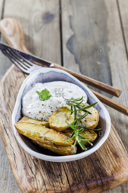 Bowl of potato wedges with rosemary and herbed curd cheese