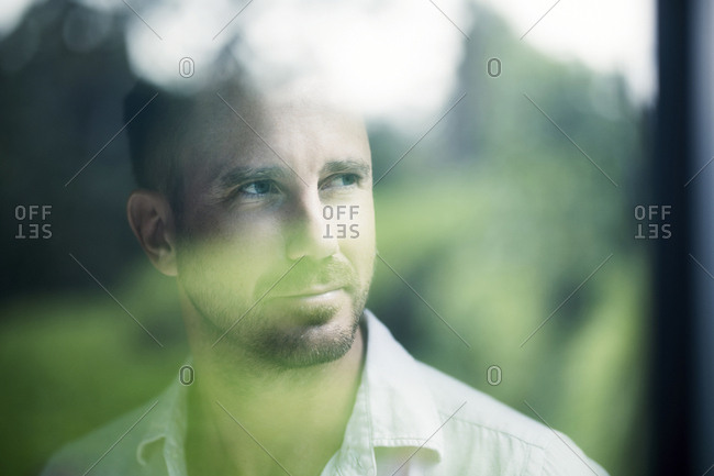 Attractive man looking through window pane- smiling- portrait