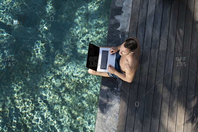 Mature man sitting at the poolside- using laptop