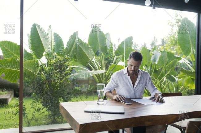 Mature man sitting at table in front of lush garden- writing