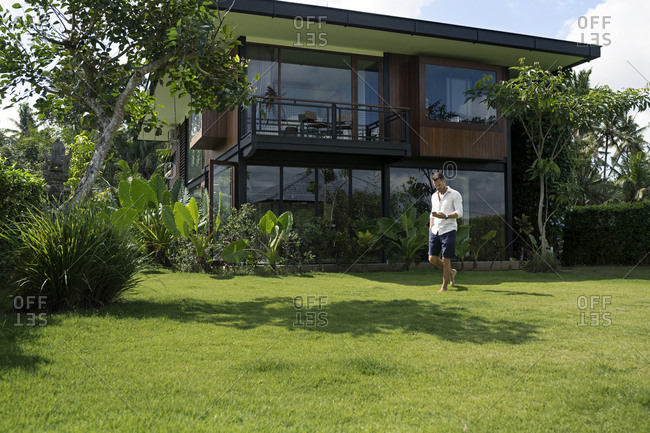 Mature man walking in garden in front of modern villa- using smartphone