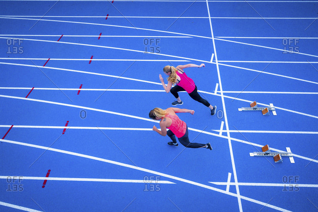 Top view of two female runners starting on tartan track