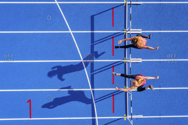 Top view of two female runners crossing hurdles on tartan track