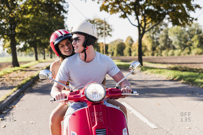 Happy young couple riding motor scooter on country road