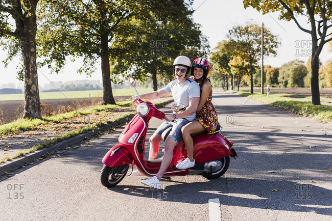 Portrait of happy young couple on motor scooter on country road