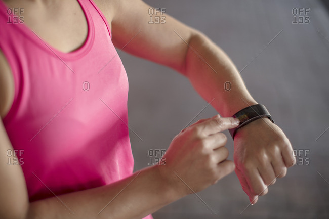 Woman adjusting settings of smart watch for outdoor training