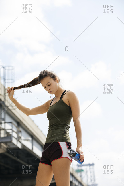 Sporty Young Woman Twisting Hair While Holding Water Bottle