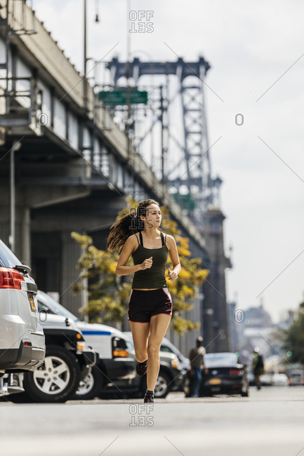 Determined Young Woman Jogging On City Street