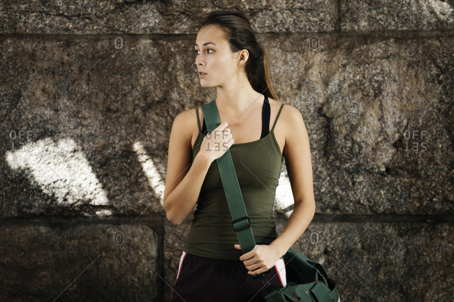 Woman In Sportswear With Shoulder Bag Standing Against Wall