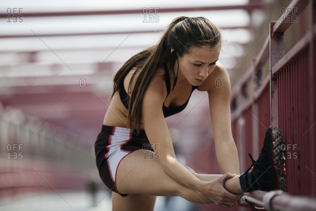 Determined Young Woman Stretching Leg On Railing