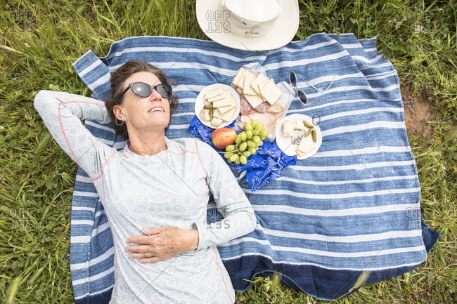 High angle view of relaxed woman lying by food on picnic blanket