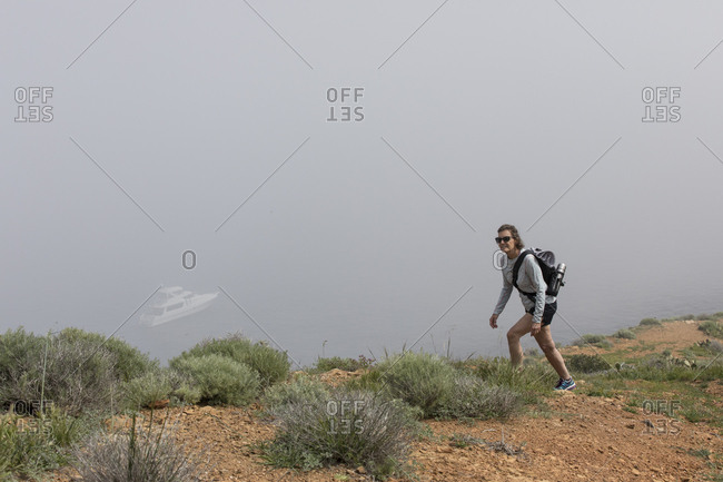 Full length of mature female hiker hiking on mountain in foggy weather