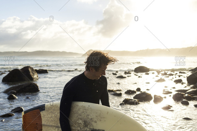 Young man tossing hair while carrying surfboard at beach during sunset