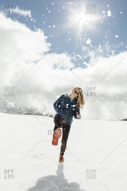Happy mid adult woman kicking snow against cloudy sky