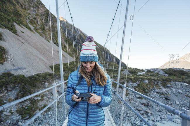 Smiling mid adult woman holding digital camera while walking on bridge