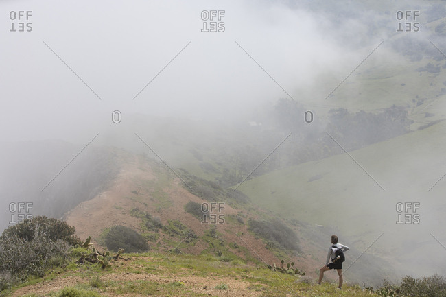 High angle view of mature woman hiking on mountain in foggy weather