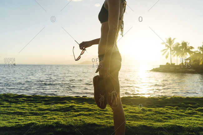 Woman in bikini holding shoes and sunglasses by water during sunset