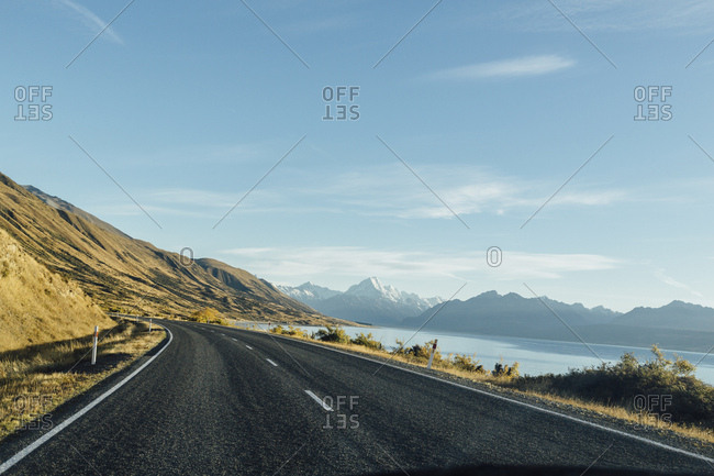 Scenic view of  empty road by mountains and lake against sky