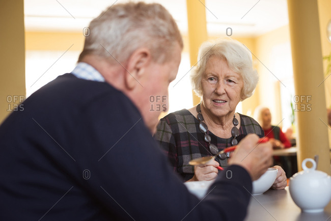 Senior friends interacting while having breakfast at nursing home