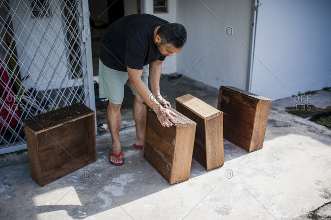 Man setting up wooden drawers for restoration