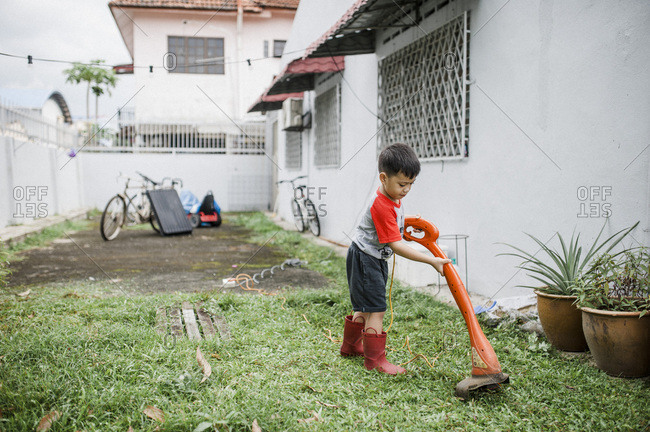 Boy using weed eater to trim grass