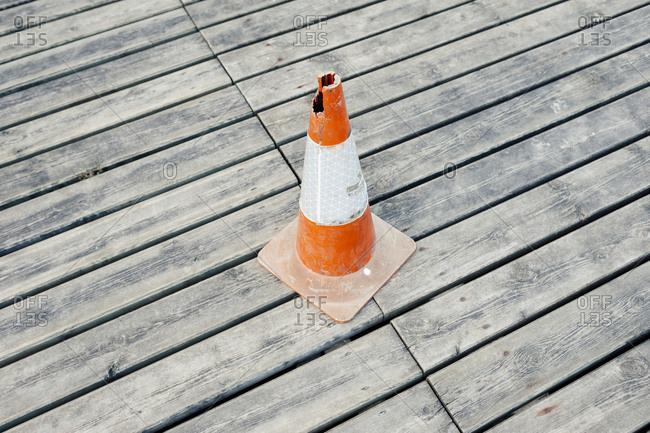 Broken traffic cone on a wooden floor