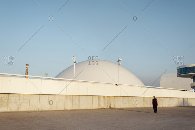 Aviles, Spain -  October 12th, 2017: Tourist walking on open square in front of domed and circular buildings in Niemeyer Center at sunset