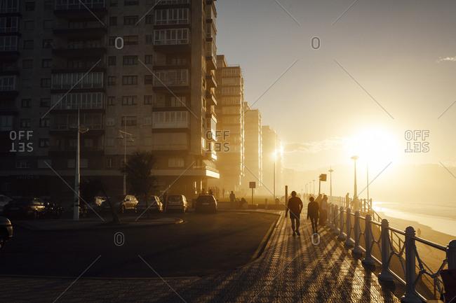Tourists walking on promenade at sunset