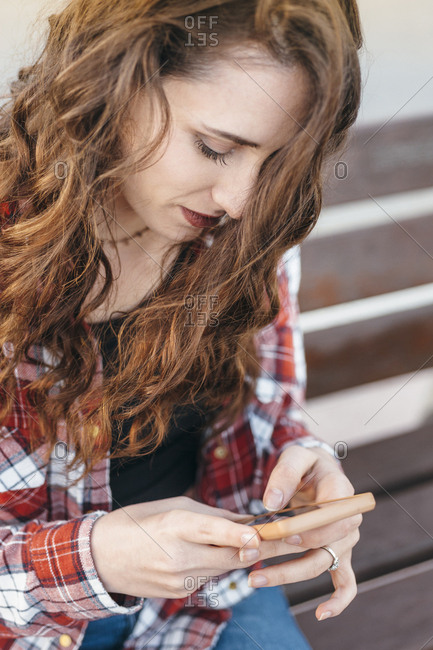 Close view of a young girl chatting by smart phone seated in a bench at afternoon in the street