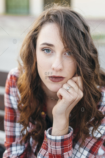 Close portrait of a confident blue eyed young girl seated in a bench at afternoon in the street