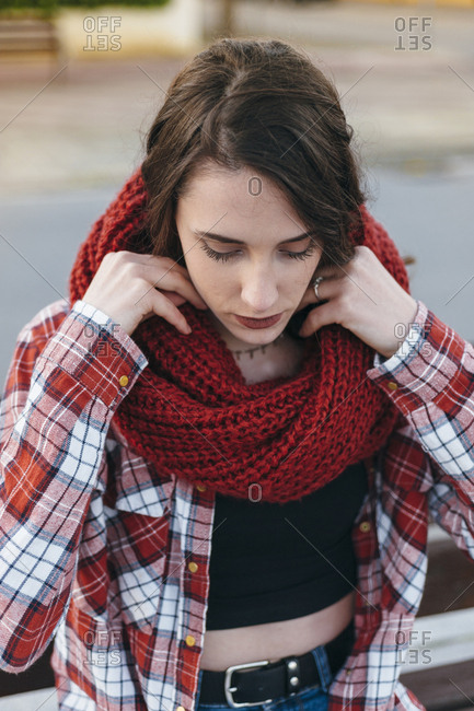 Portrait of a candid blue eyed young girl wearing a red scarf at afternoon in the street