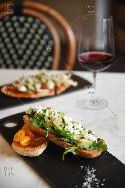 Avocado toast served with a glass of red wine