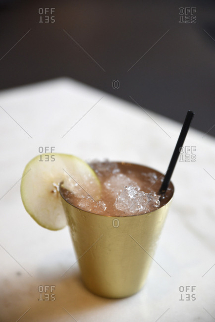 Cocktail served with crushed ice and garnished with apple slice