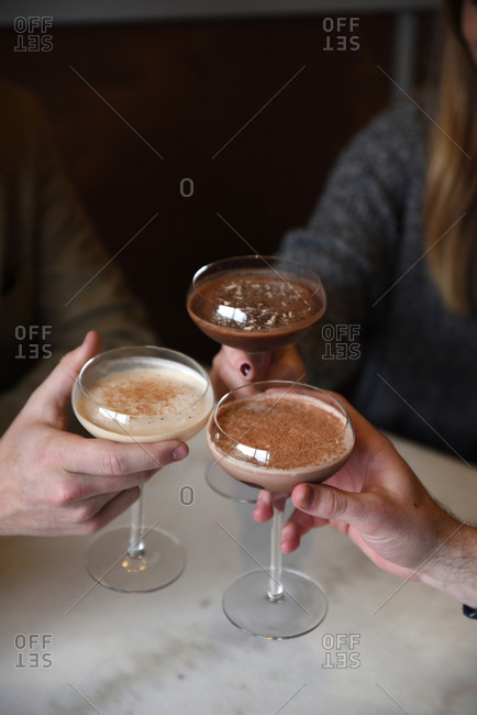 Three people holding dessert drinks