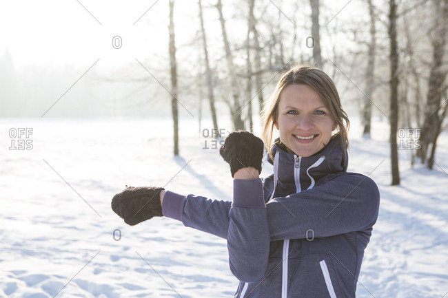 Young woman stretching in snow