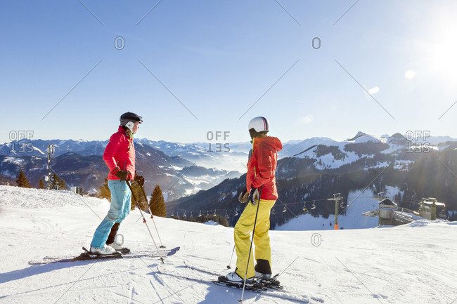 Ski holiday, Skiers overlooking mountain scenery, Sudelfeld, Bavaria, Germany